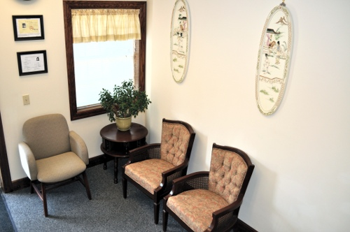 The clinic lobby, containing two chairs and a set of paintings, as well as Dr. Fu's medical certificates.